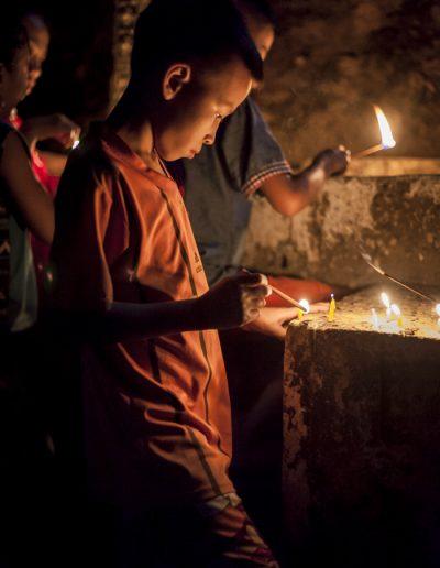 Garçon allume des bougies lors d'une célébration bouddhiste. Laos. Massimo Municchi photographe