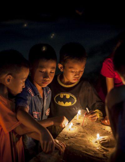 Photographie de voyage. Enfants allument des bougies lors d'une célébration bouddhiste. Nong Khiaw, Laos.
