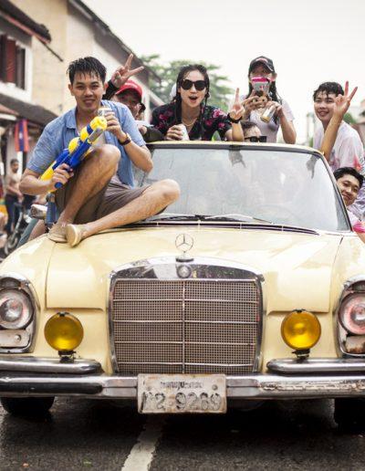Photo de voyage. Jeunes dans une vieille voiture défilent lors des célébrations de Songkran, au laos.