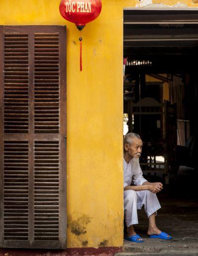 Photographie de voyage. Vieil homme assis près du seuil de sa maison, dans la ville de Hoi An, au Vietnam.