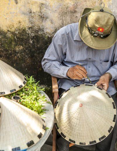 Photographie de voyage. Homme confectionne des chapeaux traditionnels dans la ville de Hoi An, au Vietnam.
