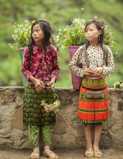 Photo de voyage. Portrait de deux filles Hmong portant des fleurs. Ha Giang loop, Vietnam. Massimo Municchi photographe.