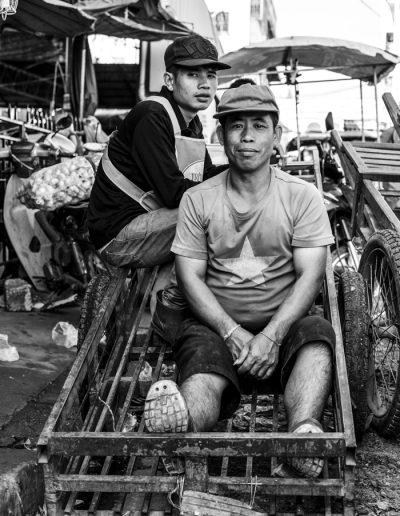Photo de voyage. Portrait noir et blanc de deux travailleurs au marché de Talat Sao. Vientiane.