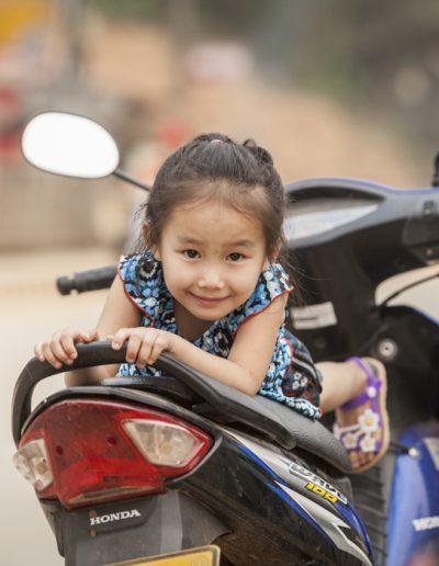 Photo de voyage.Laos. Portrait de petite fille sur un scooter.