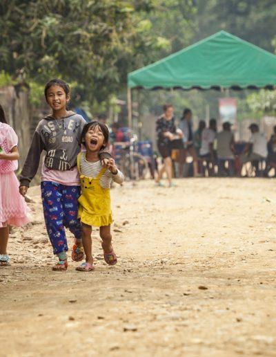 Photographie de voyage. Trois enfants se baladent dans le village de Nong Khiaw, dans le nord du Laos.