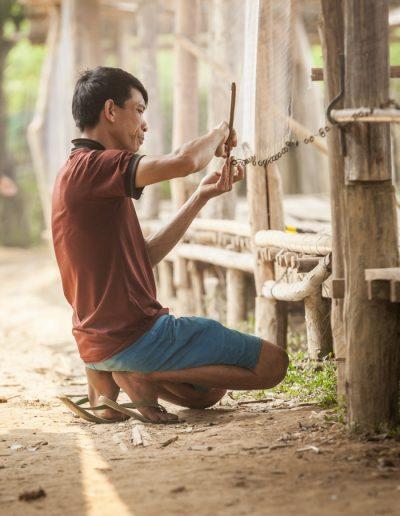 Photographie de voyage. Un pêcheur répare son filet dans le petit village de Nong Khiaw, au Laos.
